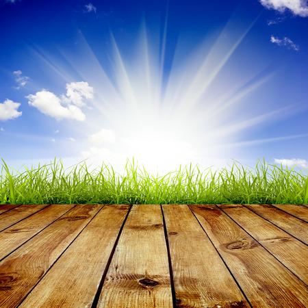 Verse lente groen gras met blauwe lucht en zonlicht en houten vloer achtergrond