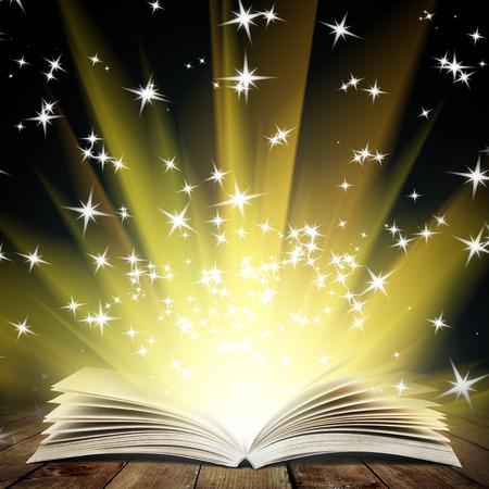 Libro abierto viejo con la luz mágica y la caída de las estrellas en los tablones de madera y oscuro fondo abstracto Foto de archivo - 34556144