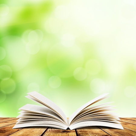 Open boek op houten planken over abstracte lichte achtergrond