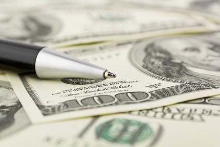 write us: Pen close-up on the dollars money background
