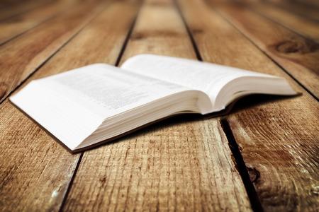 木材の背景に開いた本