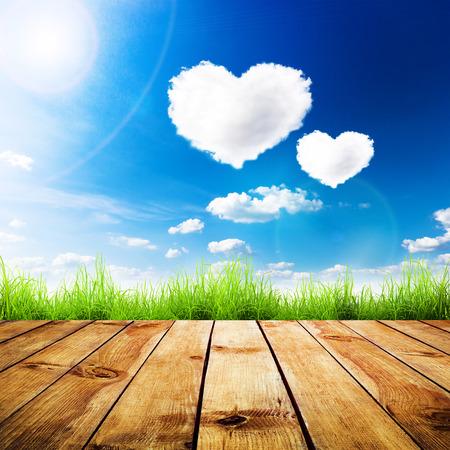 Zelená tráva na dřevěném prkně nad modrou oblohu s mraky tvaru srdce. Krása přírodního pozadí