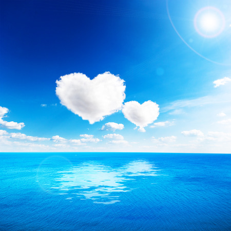 valentines day: Blue sea under clouds sky with heart shape cloud. Valentine background