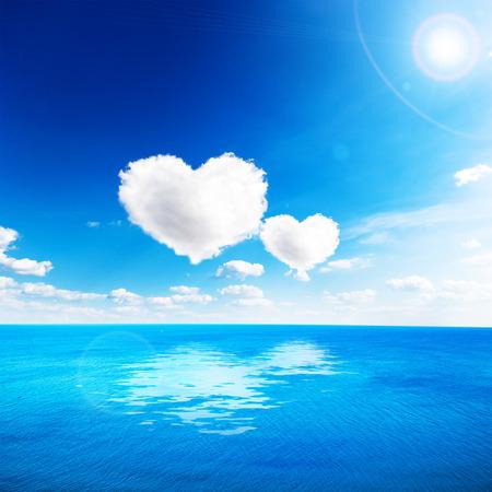 Mar azul bajo el cielo de nubes con forma de corazón de la nube. Fondo de San Valentín