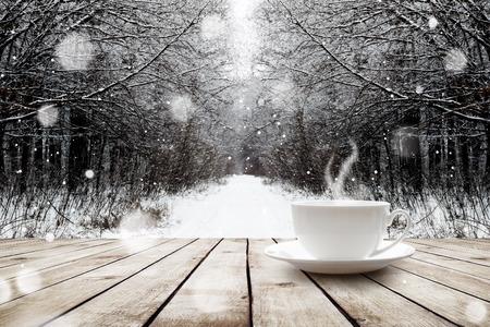 Beker met warme drank op houten tafel op de winter bos achtergrond Stockfoto