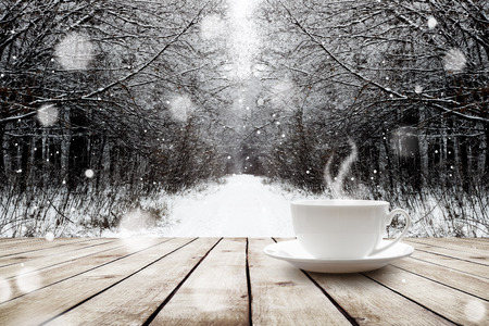 Cup with hot drink on wood table over winter forest  background