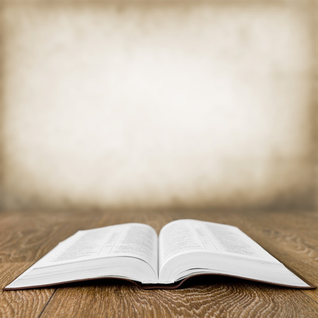 page: Open book on wood table over grunge background