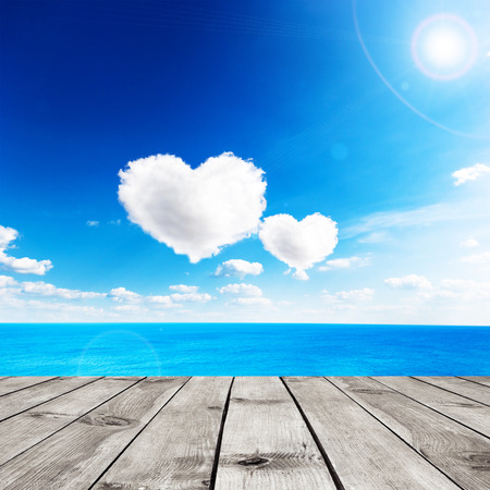 heart under: Blue sea under clouds sky with heart shape cloud and wooden pier. Valentine background