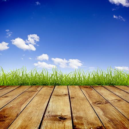 Verse lente groen gras met blauwe hemel en houten vloer achtergrond