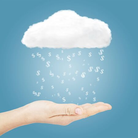 Dollar sign falling in hand from cloud over blue background photo
