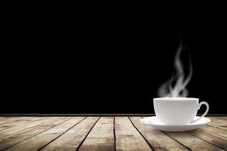 검정 배경 위에 테이블에 뜨거운 음료와 컵
