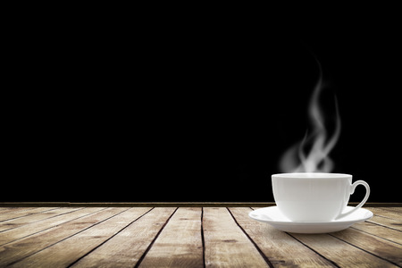 Cup with hot drink on table over black background