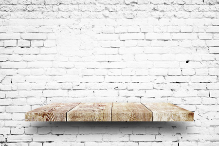Wooden shelf white brick background