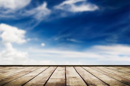 구름과 나무 널빤지 바닥 배경과 푸른 하늘