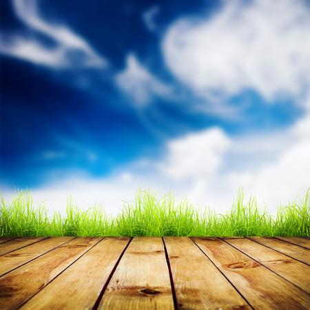 cielo despejado: Primavera de la hierba verde fresca con bokeh azul y la luz del sol y suelo de madera. Fondo natural Foto de archivo
