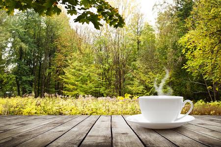 森林の背景の上の木のテーブルに温かい飲み物とカップ 写真素材