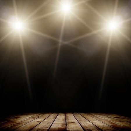 어두운 배경과 나무 바닥 위에 콘서트 스팟 조명의 ilustration입니다