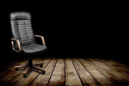 executive chair: Black leather armchair in dark room. Business interior background