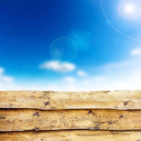 knothole: Wooden fence against blue sky background