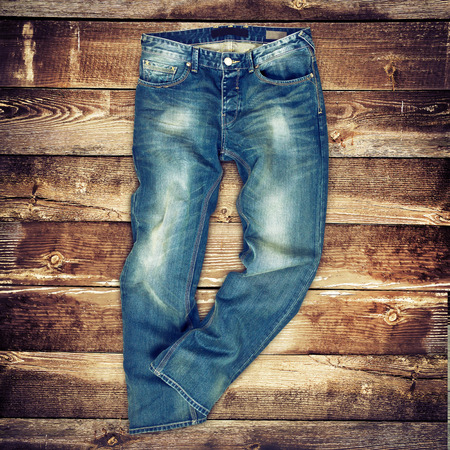 skinny jeans: Blue jeans trouser over brown wood planks background Stock Photo