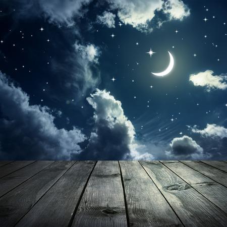Nachtelijke hemel met sterren en de maan, houten planken Stockfoto