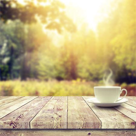 sunshine: Copa con bebida caliente en la mesa de madera sobre el fondo del bosque