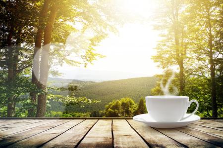 Kop met thee op tafel over bergen landschap met zonlicht. Beauty natuur achtergrond