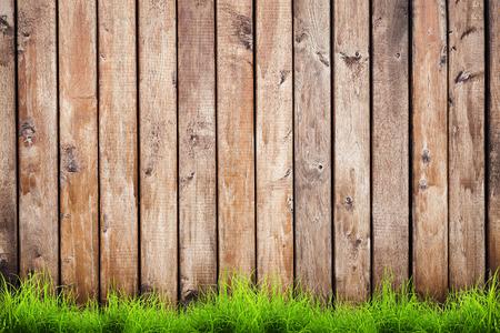 ウッド フェンスの背景の上の春の緑の草 写真素材