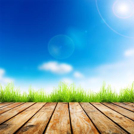 Erba fresca primavera verde con bokeh blu e la luce del sole e pavimento in legno. Sfondo naturale Archivio Fotografico - 37671050