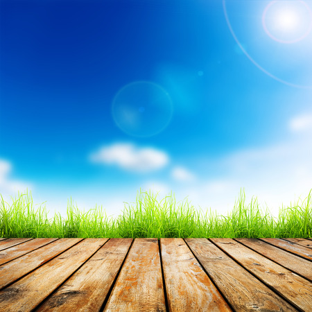 Fresh spring green grass with blue bokeh and sunlight and wood floor. Natural background