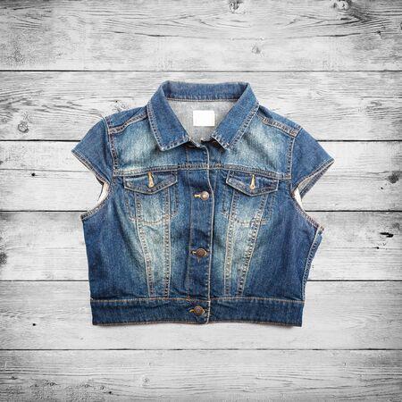 women jeans: Blue jeans jacket vest over wood background