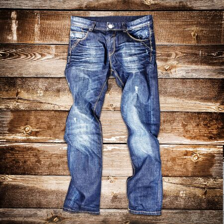 stride: Blue jeans trouser over brown wood planks background Stock Photo
