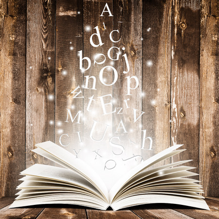 Open book with flying letters over wooden background. Magic book