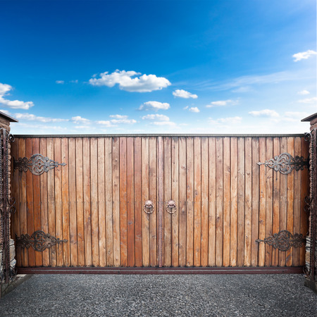 Closed wooden gates over sky background