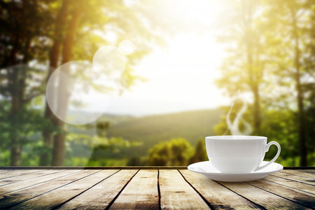 sunbeam: Cup with tea on table over mountains landscape with sunlight. Beauty nature background