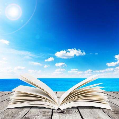 Beauty zeegezicht onder de blauwe wolken hemel. Uitzicht vanaf de houten pier. Boek op houten planken