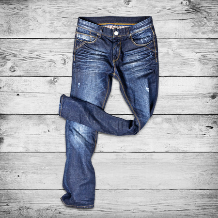 stride: Blue jeans trouser over white wood planks background