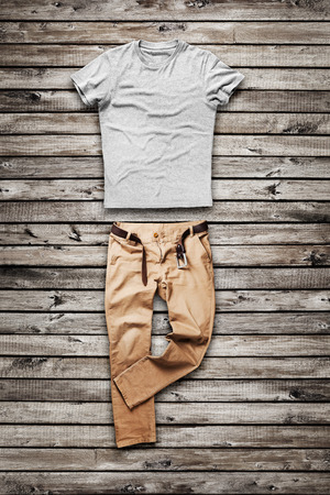 trouser: Brown jeans trouser and shirt over wood background