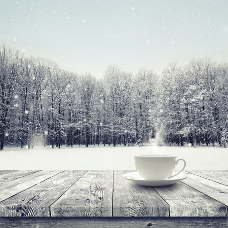 Hot drink in the cup on wooden table over winter snow covered forest. Beauty nature background Banco de Imagens