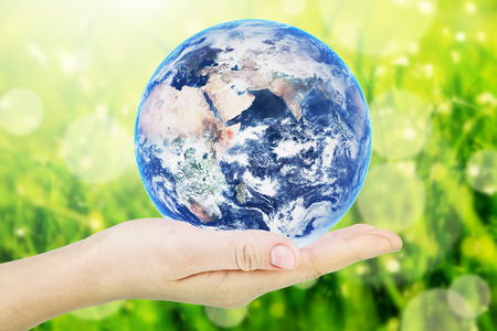 Earth planet in hand over green grass background. Elements of this image furnished by NASA