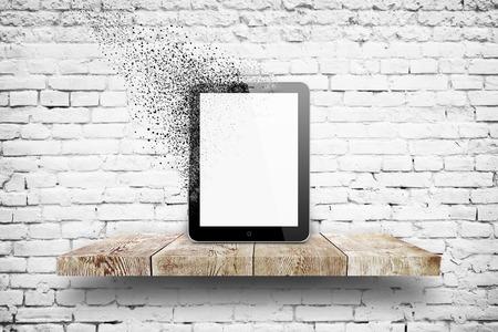 Tablet pc désintégration sur étagère en bois sur blanc fond de briques