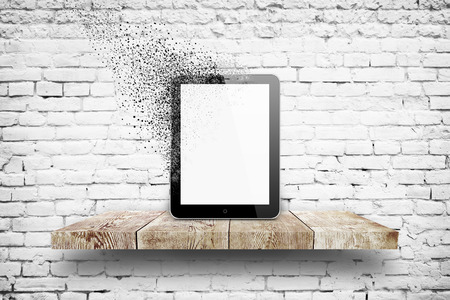 Tablet pc disintegration on wooden shelf over white brick background