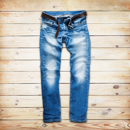 trouser: Blue jeans trouser with leather belt over white wood planks background