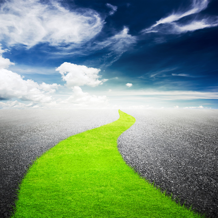 way: Green grass way over asphalted highway and blue sky with white clouds background