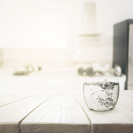 vasos de agua: Glass with water on wooden table over blured kitchen interior background