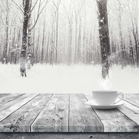 snow covered: Hot drink in the cup on wooden table over winter snow covered forest. Beauty nature background Stock Photo