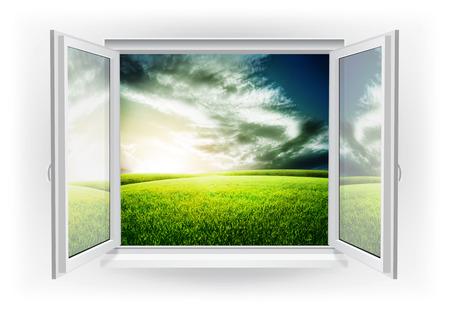 Open venster met groen veld onder zonsondergang hemel op een achtergrond