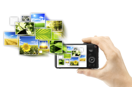 filming point of view: Closeup digital photo camera, held in hand, isolated on white background, with pictures of nature, flying from it Stock Photo