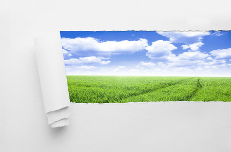 Closeup of a hole on nature background. Field with blue clouds sky