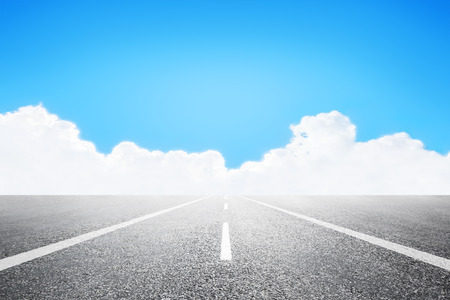vanishing point: Asphalted highway over blue sky with white clouds background